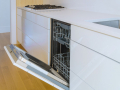Modern domestic cabinets with new appliances dishwasher in kitchen